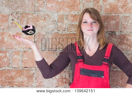 Young woman dressed in red overall is standing in front of an old brick wall. Woman is looking at the camera. Beyond her outstretched palm hand is a tape measure in space.