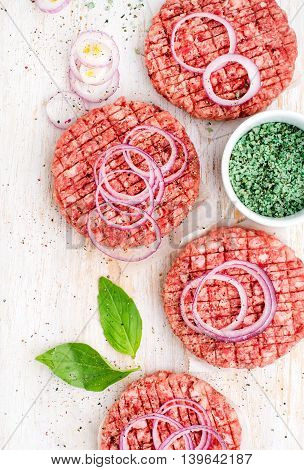 Raw ground beef meat cutlet for making burgers with onion rings and spices on white wooden background top view
