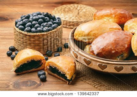 Blueberry filled yeast buns on brown wooden table.