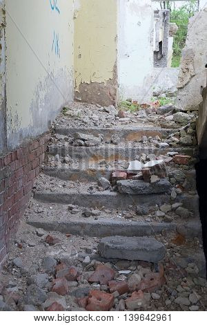 Staircase with old brick wall inside old abandoned building.