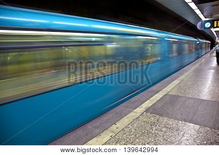 blue Train in motion arriving in the station