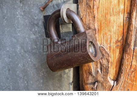Padlock on the door of a metal door close up