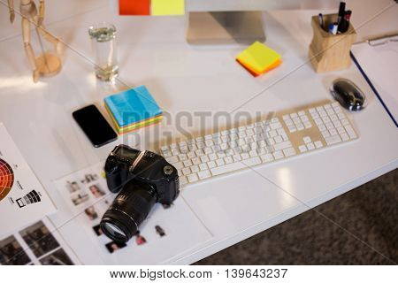 High angle view of camera by keyboard at desk in creative office