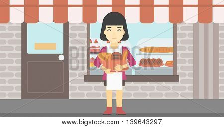 An asian  young female baker holding basket with bakery products. Female baker standing in front of bakery. Baker with bowl full of bread. Vector flat design illustration. Horizontal layout.