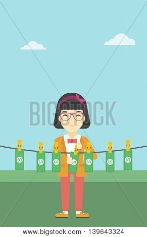 An asian young business woman drying banknotes on the clothesline on the background of blue sky. Woman loundering money. Vector flat design illustration. Vertical layout.