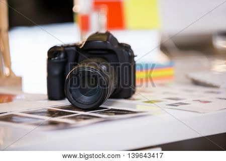 Close-up of camera on photographs at desk in creative office
