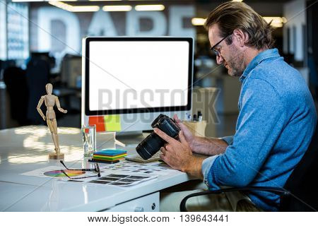 Side view of creative businessman holding camera at computer desk in office