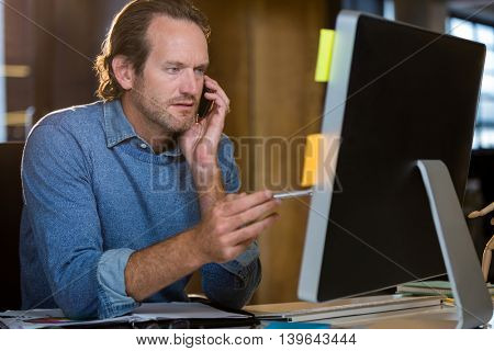 Businessman looking at monitor while talking on cellphone at desk in creative office