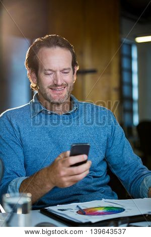 Creative businessman using cellphone at desk in office