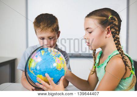School kids looking at globe in classroom at school
