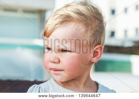 Outdoor Portrait Of Serious Cute Blond Baby Girl