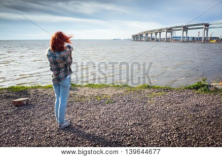 Teenage Girl With Red Hair Taking Photo On Phone