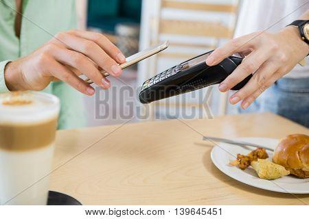 Customer making payment through smartphone in restaurant