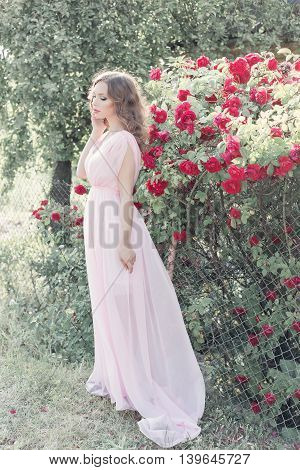 beautiful sexy girl in a light dress with delicate make-up and hair in a flower garden with roses in luchas sunlight at sunset. Styled photo fane art