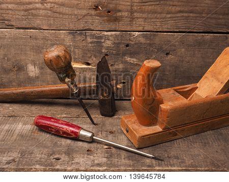 Old used wood worker tools on a rustic wooden background