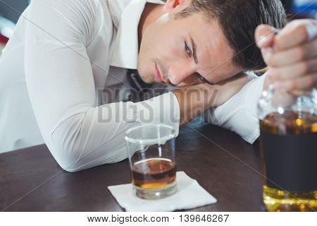 Drunken man lying on a bar counter at restaurant
