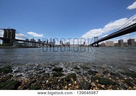 NEW YORK - JULY 21, 2016: Panoramic view of Manhattan between Brooklyn Bridge (L) and  Manhattan Bridge