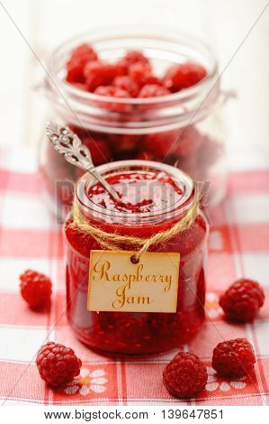 Raspberry jam in glass jar and raspberries. Selective focus.