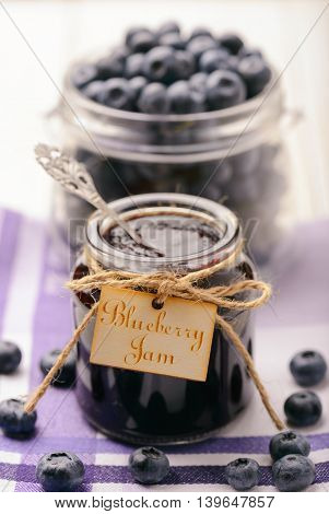 Blueberry jam in glass jars and blueberries. Selective focus.