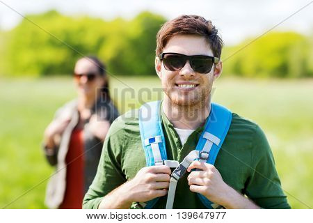 travel, hiking, backpacking, tourism and people concept - happy couple with backpacks walking outdoors