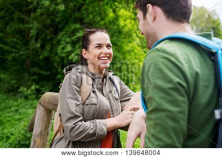 travel, hiking, backpacking, tourism and people concept - smiling couple with backpacks talking in nature