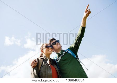travel, hiking, backpacking, tourism and people concept - happy couple with backpacks outdoors pointing finger to something in sky