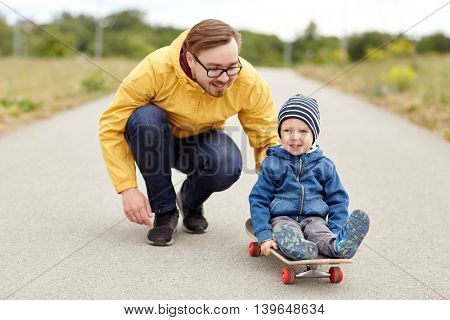 family, childhood, fatherhood, leisure and people concept - happy father and little son riding on skateboard