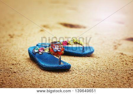 Beach flip flops on tropical sandy coast. Holiday concept.
