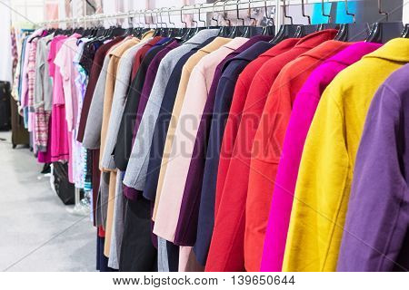 Multi-colored coat hanging on hangers. Shopping malls.