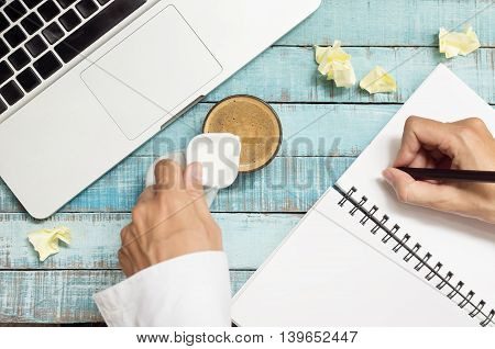 hands pouring milk in coffe cup and writing in notebook on workplace. Coffee break concept. Hands in frame.