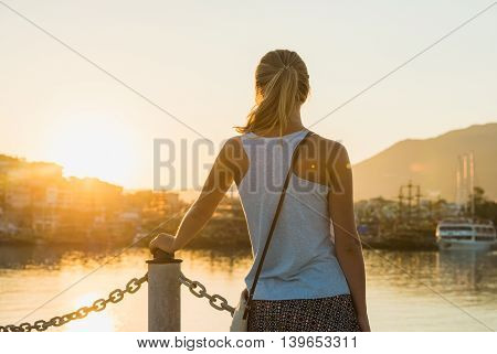 Young blond woman watching sunset in sea port of Alanya Turkey Mediterranean region.