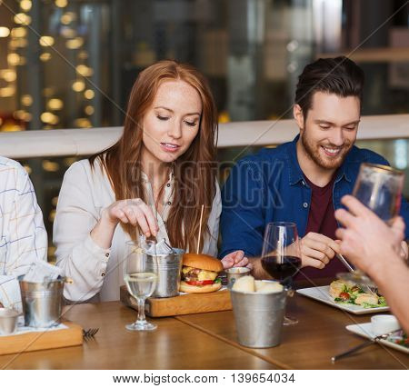 leisure, technology, lifestyle and people concept - happy man with smartphone and friends dining at restaurant