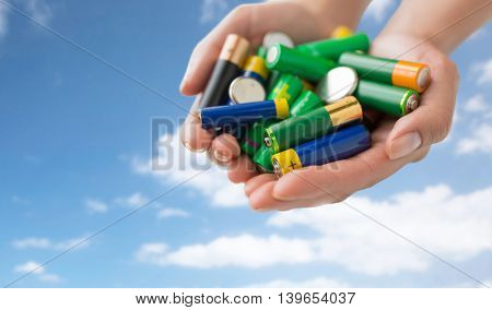 recycling, energy, power, environment and ecology concept - close up of hands holding alkaline batteries heap over blue sky and clouds background