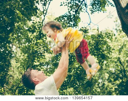 Dad and his little one-year old daughter having fun. Father throws up his little girl. Colorful image for modern life family concept