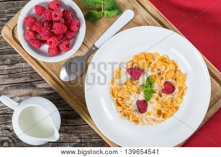 crispy corn flakes with raspberry and milk in plate decorated with mint on wooden worktop traditional and quick breakfast close-up view from above