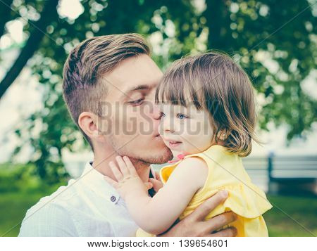 Close up of father holding his crying daughter. Dad kissing his little daughter