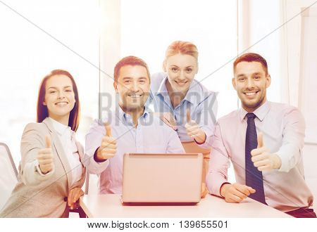 business and office concept - smiling business team working with laptop computer in office showing thumbs up