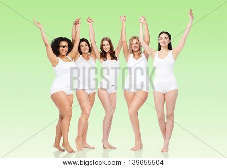 happiness, friendship, beauty, body positive and people concept - group of happy different women in white underwear with raised arms celebrating victory over green natural background
