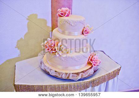 Pink wedding cake on table at wedding