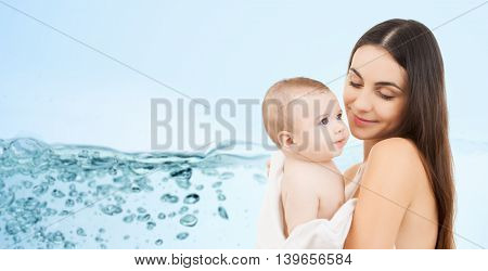 family, motherhood, people and child care concept - happy mother holding adorable baby over blue background with water splash