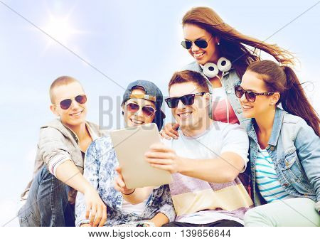 summer holidays, teenage and technology concept - group of teenagers taking picture with tablet pc