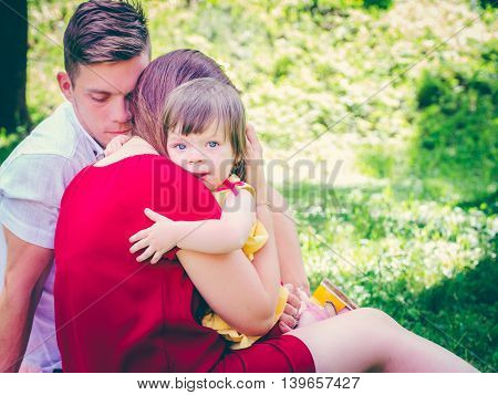 Mother holding her crying one-year old baby girl. Sad expression - family concept