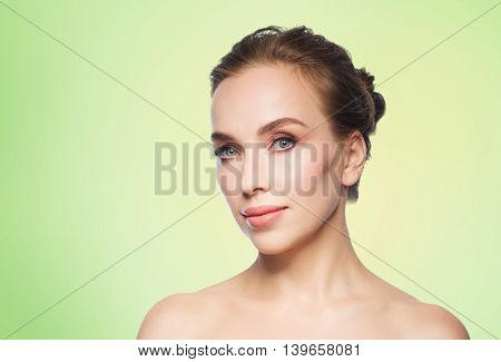 beauty, people and health concept - beautiful young woman face over green background