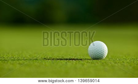 Selective Focus. White Golf Ball Near Hole On Green Grass Good For Background