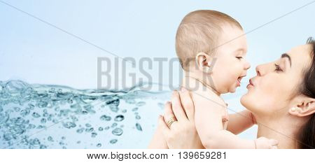 family, motherhood, people and child care concept - happy mother kissing adorable baby over blue background with water splash