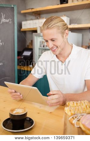Waiter using digital tablet in cafeteria
