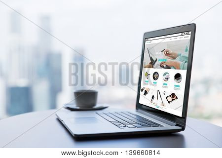 internet shopping, technology, business and modern life concept- close up of open laptop computer with online shop web page on screen on table