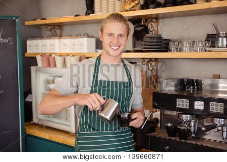 Waiter pouring coffee in a cup at cafeteria
