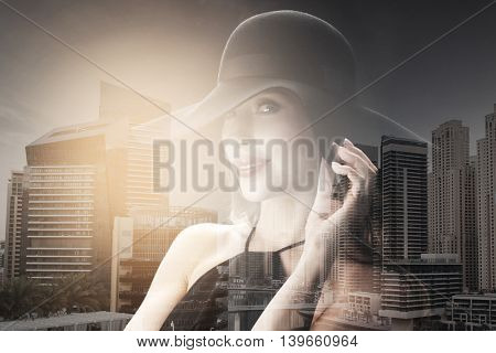 people, luxury and fashion concept - beautiful woman in black hat over dubai city with double exposure background