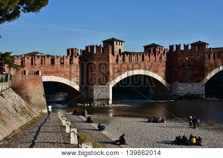 VERONA, ITALY - FEBRUARY 5: Verona people on Adige river bank and medieval Scaliger Bridge FEBRUARY 5, 2016 in Verona, Italy